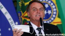 Brazil's President Jair Bolsonaro holds his protective face mask during a ceremony at the Planalto Palace, amid the coronavirus disease (COVID-19) pandemic, in Brasilia, Brazil, June 10, 2021. REUTERS/Adriano Machado
