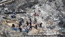Such- und Rettungskräfte suchen nach Überlebenden in den Trümmern im dem teilweise eingestürzten zwölfstöckigen Gebäude. Nach dem Teileinsturz eines zwölfstöckigen Wohnhauses im US-Bundesstaat Florida erschwert ein Feuer die Suche nach Vermissten. +++ dpa-Bildfunk +++