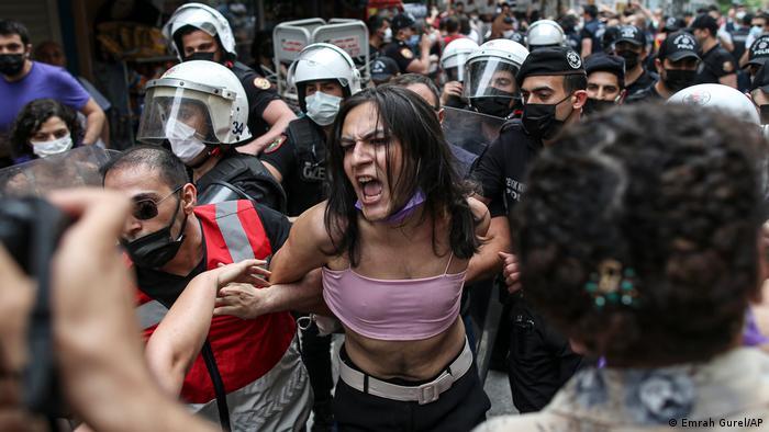 Policiais seguram mulher, que grita. Atrás dela, há muitos policiais.