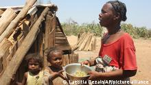 Toharano, mother of 18 children, with two of her children, holds a bowl in the village of Ankilimarovahatsy, Madagascar, Monday, Nov. 9, 2020. As a consequence of three straight years of drought, along with historic neglect by the government of the remote region as well as the COVID-19 pandemic,1.5 million people are in need of emergency food assistance, according to the U.N. World Food Program.(AP Photo/Laetitia Bezain)