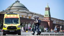 Russian National Guard (Rosgvardia) servicemen wearing face masks walk along Red Square past an ambulance in central Moscow on June 18, 2021, amid the crisis linked with the Covid-19 pandemic. - Moscow hits a new record confirmed 9,056 new Covid-19 daily cases as apart of 17,262 cases in Russia overall. (Photo by Alexander NEMENOV / AFP)