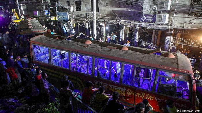 People gather around a damaged bus following an explosion in Dhaka, Bangladesh