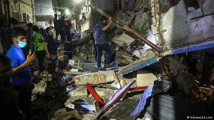 People search through the rubble of a building following an explosion in Dhaka, Bangladesh