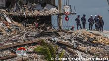 """*** Dieses Bild ist fertig zugeschnitten als Social Media Snack (für Facebook, Twitter, Instagram) im Tableau zu finden: Fach """"Images"""" —> Weltspiegel/Bilder des Tages *** TOPSHOT - Search and Rescue teams look for possible survivors in the partially collapsed 12-story Champlain Towers South condo building on June 27, 2021 in Surfside, Florida. - The death toll after the collapse of a Florida apartment tower has risen to nine, the local mayor said on June 27, 2021, more than three days after the building pancaked as residents slept. We were able to recover four additional bodies in the rubble... So I am confirming today that the death toll is at nine, Miami-Dade County mayor Daniella Levine Cava told reporters in Surfside, near Miami Beach, adding that one victim had died in hospital. We've identified four of the victims and notified next of kin. (Photo by Giorgio Viera / AFP) (Photo by GIORGIO VIERA/AFP via Getty Images)"""