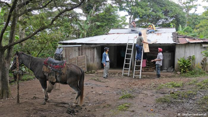 Ein Bauernhaus in Miraflores in Nicaragua. Ein Pferd steht davor. Dahinter montieren Techniker ein Solarmodul auf das Dach.