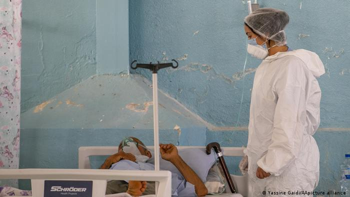 Person in white protective suit, surgical cap and face mask peers down at patient in a bed in front of a rough blue wall