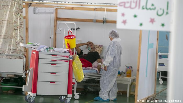 Person in white protective suit looks at a patient in a bed in a makeshift cubicle, cart with medical appliances in the front