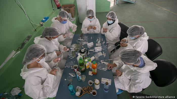 View from above, seven people in white protective suits sit around a table