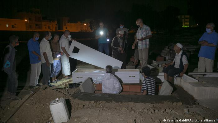 Graveyard in Tunisia in the dark,men stand around, one holds lid of a coffin
