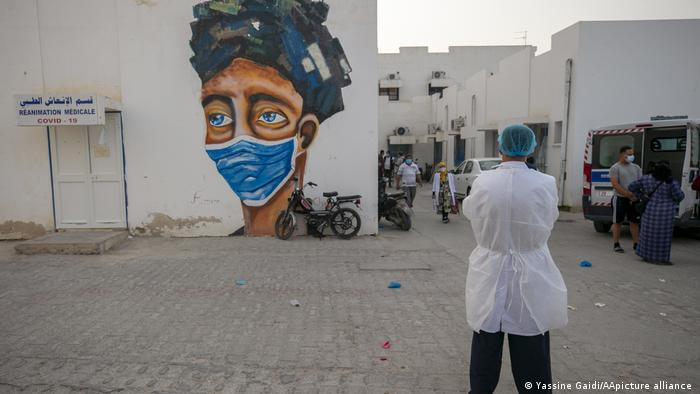 Person wearing a white lab coat and a green surgical cap watches a few other people among square white buildings, one with a large graffiti of a face with a face mask