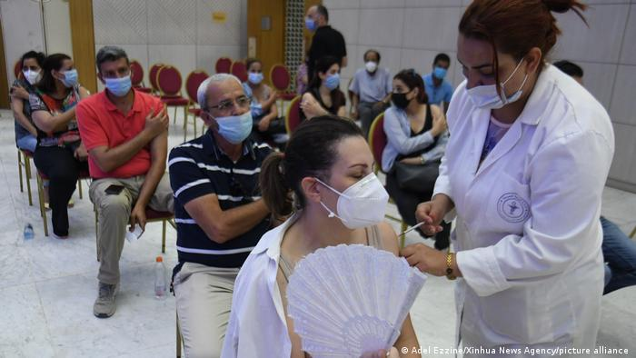 People seated on chairs, wearing face masks, a woman at the front is being vaccinated by female staff