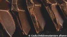 Closeup of broken dark chocolate blocks stack on black background