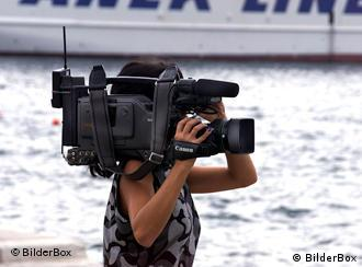 A woman holding a television camera