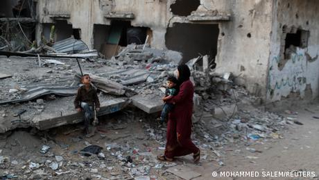 A Palestinian woman holding her son walks past her house that was destroyed by an Israeli air strike in June. There is another boy say on a bit of debris. The building next door is also highly damaged.