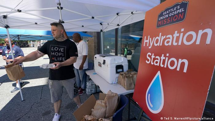 Carlos Ramos hands out bottles of water and sack lunches as he works at a hydration station in front of the Union Gospel Mission in Seattle