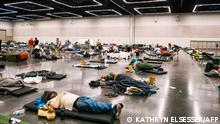 People rest at the Oregon Convention Center cooling station in Oregon, Portland on June 28, 2021, as a heatwave moves over much of the United States. - Swathes of the United States and Canada endured record-setting heat on June 27, 2021, forcing schools and Covid-19 testing centers to close and the postponement of an Olympic athletics qualifying event, with forecasters warning of worse to come. The village of Lytton in British Columbia broke the record for Canada's all-time high, with a temperature of 46.6 degrees Celsius (116 Fahrenheit), said Environment Canada. (Photo by Kathryn Elsesser / AFP)