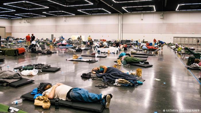 Leute liegen in einer Turnhalle auf Matten