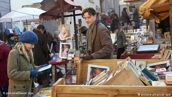 Actors from Inkheart stand in a crowded market place in this still from the movie