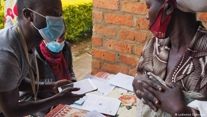 A research nurse in Rwanda talking to a woman about the DYNAMIC/ePOCT+ study