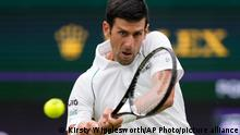 Serbia's Novak Djokovic returns the ball to Britain's Jack Draper during the men's singles match on day one of the Wimbledon Tennis Championships in London, Monday June 28, 2021. (AP Photo/Kirsty Wigglesworth)