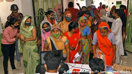 A group of women standing around waiting to register for a vaccination appointment in Rajasthan