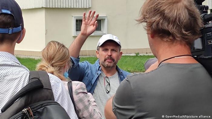Roman Badanin winkt Journalisten nach dem Verlassen des Polizeigebäudes