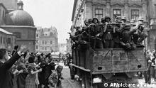 Inhabitants of the former Soviet-occupied Polish city of Lwow wave at a passing truckload of German soldiers as Nazi troops take over the city on July 2, 1941, according to thecaption passed through German government censors. The city is now known as Lviv in Ukraine.(AP Photo)