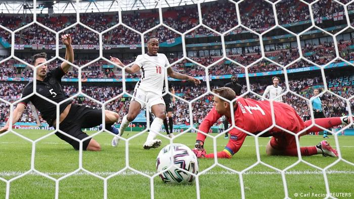 تیم ملی فوتبال آلمان در دور یکهشتم نهایی در ورزشگاه ومبلی به مصاف انگلیس رفت. ملیپوشان آلمان در این دیدار که در حضور ۴۵ هزار تماشاگر برگزار شد، با نتیجه ۲ بر صفر از انگیس شکست خورد و از گردونه رقابتها حذف شد. تصویری از نخستین گل انگلیس به آلمان که توسط استرلینگ (پیراهن سفید) به ثمر رسید. ماتس هوملز (چپ) و مانوئل نویر، دروازهبان آلمان علیرغم تلاش فراوان نتوانستند مانع از این گل شوند.