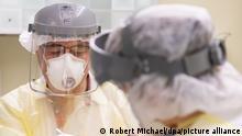 ILLUSTRATION - Zahnarzt Conrad Kühnöl (l) behandelt mit Visier, FFP3 Atemschutzmaske und Virenschutzkittel mit seinen Zahnmedizinischen Fachangestellten einen Corona-Patienten in seiner Zahnrztpraxis. (gestellte Szene)