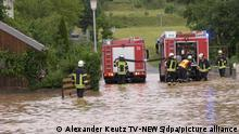 29/06/2021 Einsatzkräfte der Feuerwehr stehen auf einer durch ein Unwetter überfluteten Straße.