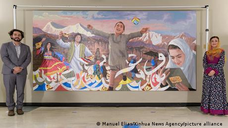 عادله راز و امید شریفی در کنار تابلوی نصب شده در مقر سازمان ملل متحد.