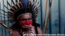 An Indigenous man wears a mask amid the COVID-19 pandemic that reads in Portuguese Get out Bolsonaro during a protest against Brazilian President Jair Bolsonaro's proposals to allow mining on Indigenous lands, at the entrance of the Chamber of Deputies in Brasilia, Brazil, Wednesday, June 16, 2021. (AP Photo/Eraldo Peres)