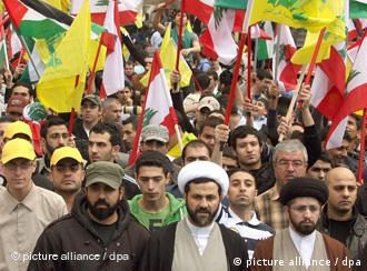 Lebanese and Palestinian demonstrators hold flags of the Hezbollah, Lebanon and Palestine as they take part in a rally in front of the United Nations House in Beirut, Lebanon