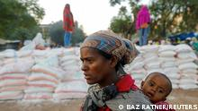 ARCHIV +++ FILE PHOTO: A woman carries an infant as she queues in line for food, at the Tsehaye primary school, which was turned into a temporary shelter for people displaced by conflict, in the town of Shire, Tigray region, Ethiopia, March 15, 2021. REUTERS/Baz Ratner/File Photo