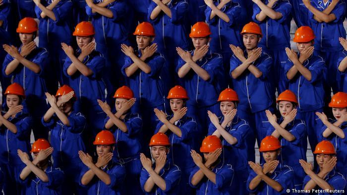 Artistas vestidos como 'obreros' en la celebración del centenario en Pekín.