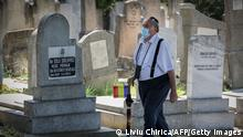 A member of the Jewish community walks at the Jewish cemetery in the city of Iasi, Romania, on June 29, 2021. - Romania commemorates the 80th anniversary of the Iasi pogrom initiated by the Romanian governmental forces under Marshal Ion Antonescu in the city of Iasi, northeastern Romania, against its Jewish comunity. According to Romanian authorities around 15,000 Romanian jews were massacred in the pogrom itself or in its aftermath and many jews were deported. (Photo by Liviu Chirica / AFP) (Photo by LIVIU CHIRICA/AFP via Getty Images)