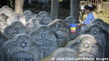 TOPSHOT - A child wearing a kippah and holding a Romanian flag walks past tombstones at the Jewish cemetery in the city of Iasi, Romania, on June 29, 2021. - Romania commemorates the 80th anniversary of the Iasi pogrom initiated by the Romanian governmental forces under Marshal Ion Antonescu in the city of Iasi, northeastern Romania, against its Jewish comunity. According to Romanian authorities around 15,000 Romanian jews were massacred in the pogrom itself or in its aftermath and many jews were deported. (Photo by Liviu CHIRICA / AFP) (Photo by LIVIU CHIRICA/AFP via Getty Images)