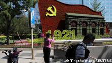 21.06.21 *** A woman uses her phone in front of a flower installation marking the 100th anniversary of the founding of the Chinese Communist Party of China, in Beijing, China June 21, 2021. Picture taken June 21, 2021. REUTERS/Tingshu Wang