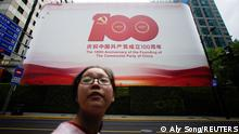 28.06.21 *** A woman walks on a street in front of a signboard marking the 100th founding anniversary of the Communist Party of China, ahead of the 100th anniversary of the Communist Party of China, in Shanghai, China June 28, 2021. Picture taken June 28, 2021. REUTERS/Aly Song