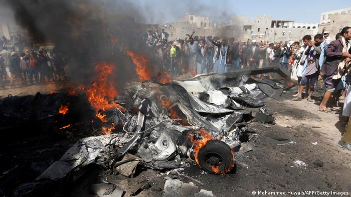 Yemenis gather around burning wreckage of a drone in the country's capital Sanaa