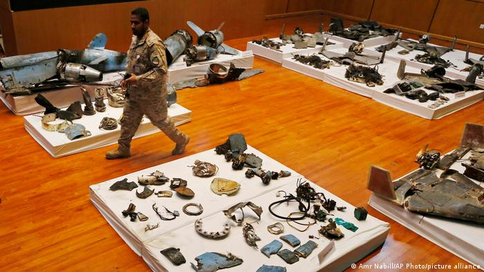 A Saudi military officer walking by remains of Iranian cruise missiles and drones used in an attack on Saudi Arabia's oil industry
