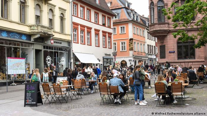 People sitting at outdoor tables at a cafe in Heidelberg, Germany