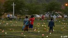 TOPSHOT - A family walks through a field where flags and solar lights now mark the site where human remains were discovered in unmarked graves at the former Marieval Indian Residential School site on Cowessess First Nation, Saskatchewan on June 26, 2021. - More than 750 unmarked graves have been found near a former Catholic boarding school for indigenous children in western Canada, a tribal leader said Thursday -- the second such shock discovery in less than a month. (Photo by Geoff Robins / AFP)