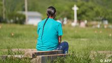A man man sits and prays at the field where the remains of over 750 children were buried on the site of the former Marieval Indian Residential School in Cowessess First Nation, Saskatchewan, June 25, 2021. - More than 750 unmarked graves have been found near a former Catholic boarding school for indigenous children in western Canada, a tribal leader said Thursday -- the second such shock discovery in less than a month. The revelation once again cast a spotlight on a dark chapter in Canada's history, and revived calls on the Pope and the Church to apologize for the abuse suffered at the schools, where students were forcibly assimilated into the country's dominant culture. (Photo by Geoff Robins / AFP)