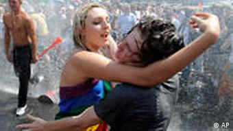 A couple dances in a sprinkler during the Euro Pride gay parade in Warsaw, Poland, Saturday, July 17, 2010.