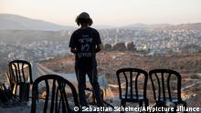 An Israeli settler stands at the outpost of Eviatar near the northern West Bank town of Nablus, Wednesday, June 30, 2021. Israel has reached a compromise with Jewish settlers who rapidly established an unauthorized outpost in the occupied West Bank last month, officials and the settlers said Wednesday. Hebrew reads: My country will not be divided.(AP Photo/Sebastian Scheiner)