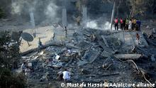 KHAN YUNIS, GAZA - JULY 8: Palestinians inspect destroyed area as smoke rises from the ruins in Khan Yunis after the Israeli airstrikes aiming Gaza on July 8, 2014. Mustafa Hassona/Anadolu Agency