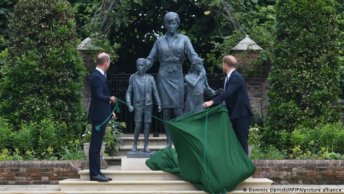 William e Harry retiram pano verde que cobria a estátua. Eles observam a estátua que retrata a mãe, com duas crianças, uma menina e um menino.