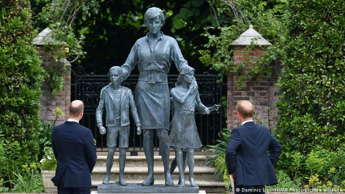 Princes William and Harry standing in front of the statue.