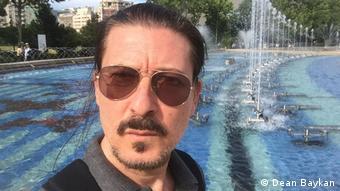 Schauspieler Dean Baykan steht vor einem Brunnen